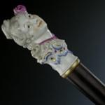 """Canna con manopola in porcellana finemente modellata e dipinta in forma di testa di ragazza con una rosa tra i capelli, """"Nymphenburg"""" da un modello di Bustelli."""